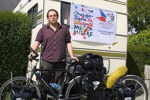 Derrière Loïc Kerouanton et son vélo équipé trône le drapeau du Secours populaire. Il sera en fond des photographies qu'il compte prendre avec ses futures rencontres.