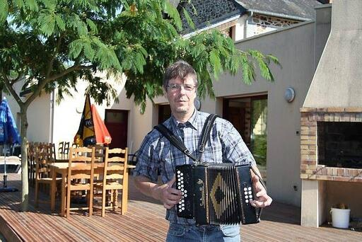 Bruno Chemin, ici devant son restaurant, a appris l'accordéon pour en jouer pendant qu'il conte.