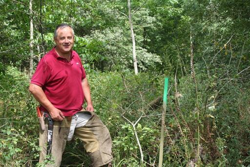 Hubert Guillais devant le piquet vert qui délimite le tracé sur le terrain : « toute cette plantation va passer à la moulinette ! » Photo