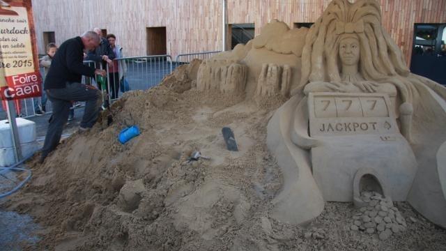 photo dale murdock sculpte sur le sable une représentation du thème de la foire internationale de caen 2015. © ouest-france